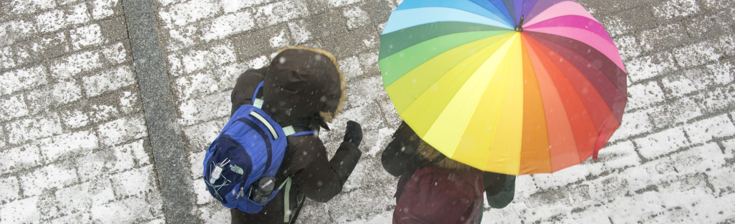 Overhead picture of two people walking on a lightly snow covered sidewalk, one person is holding a rainbow colored umbrella.